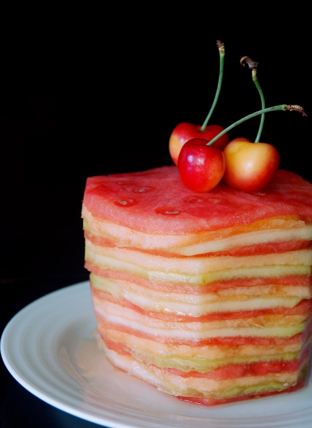 Fresh Melon Cake on a white plate with three yellow and red cherries on top