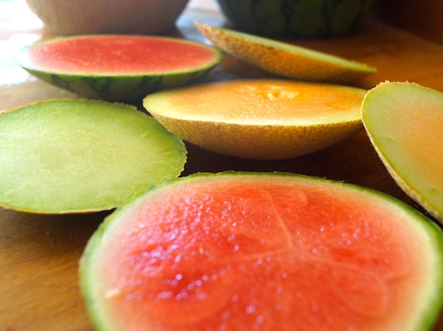 Melon slices in varying colors on cutting board
