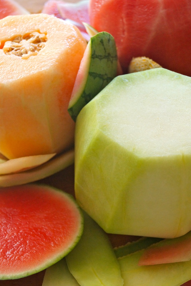 Melons in varying colors with skin removed on cutting board