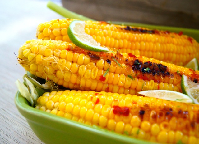 Grilled Chile-Lime Corn on the Cob on a bright green baking dish with bits of red pepper and lime slices on top.