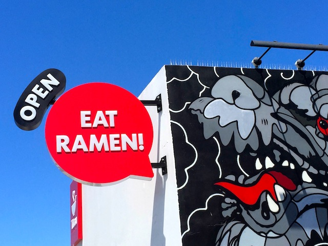 The mural of a dragon and open sign on the outside of Tatsu Ramen Restaurant in Los Angeles.