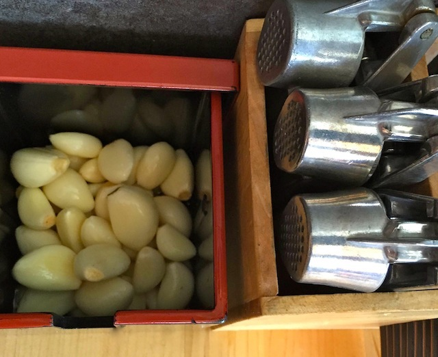 Fresh, whole garlic condiment and silver garlic presses on the table at the Los Angeles Tatsu Ramen Restaurant.