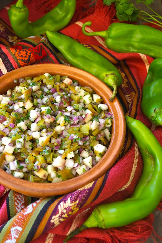 Roasted Hatch Chile Peach Salsa in a round, teracotta dish with several bright green Hatch Chiles on a Mexican-style cloth.