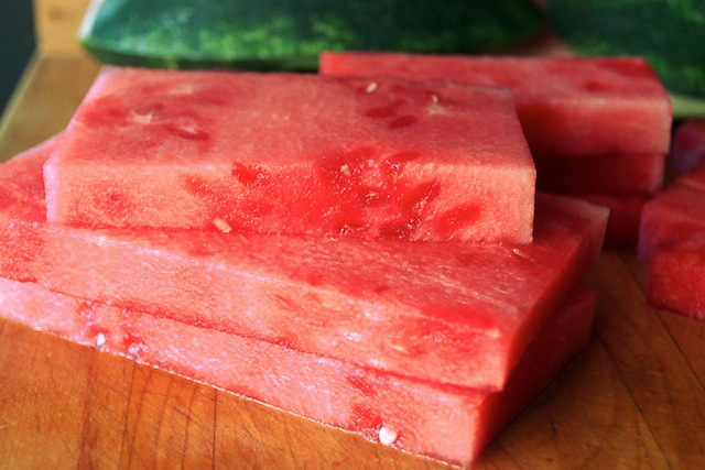 Thick, rectangular and square cuts of watermelon on a cutting board.