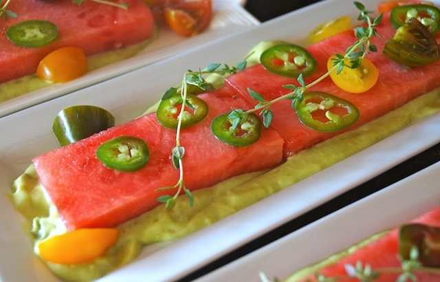 white, rectangular plate with Compressed Watermelon Salad with thin jalapeno slices on top.
