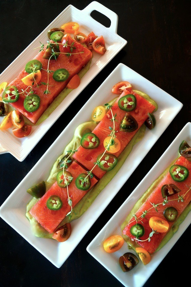 Three white, rectangular plates with Compressed Watermelon Salad with thin jalapeno slices, multi-colored tomatoes and fresh thyme. on top.