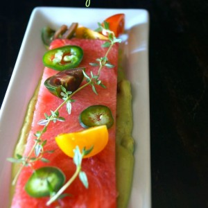 Compressed Watermelon Tomato and Jalapeño Salad With Creamy Lemon-Lime Avocado Dressing on narrow white plate