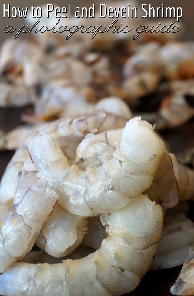 A pile of raw shrimp with shells behind them.