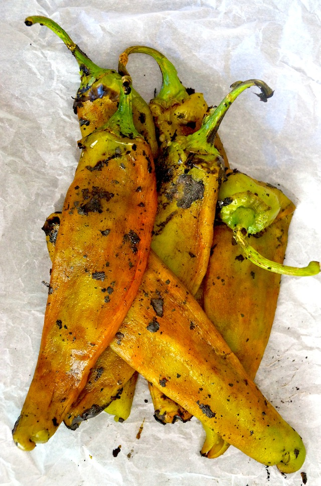 pile of several peeled, roasted Hatch Chilies on parchment paper.