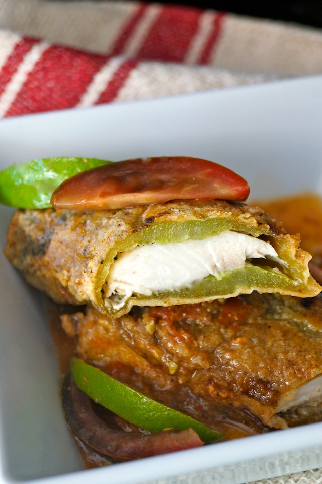 Mahi Mahi Stuffed Roasted Hatch Chiles with Tomato Lime Sauce in a shallow, square white bowl with fresh lime and tomato slices as garnish.