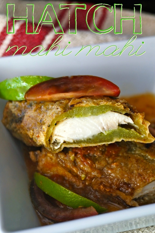 Mahi Mahi Stuffed Hatch Chiles with Tomato Lime Sauce on a white plate with tomato and lime slices.