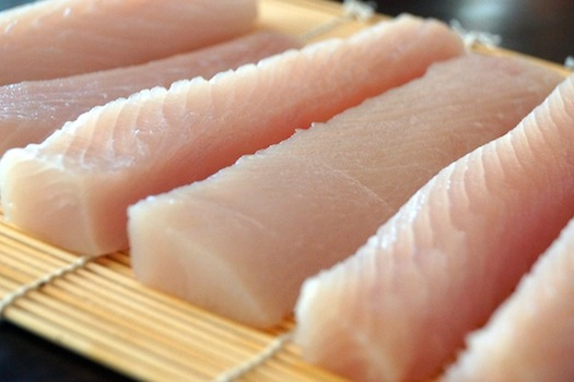 Several fillets of fresh Mahi Mahi on a sushi mat.