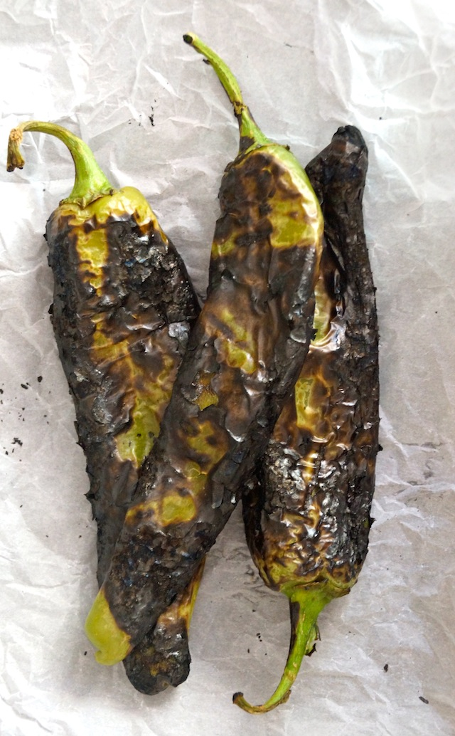 3 charred hatch chiles on crumbled parchment paper.