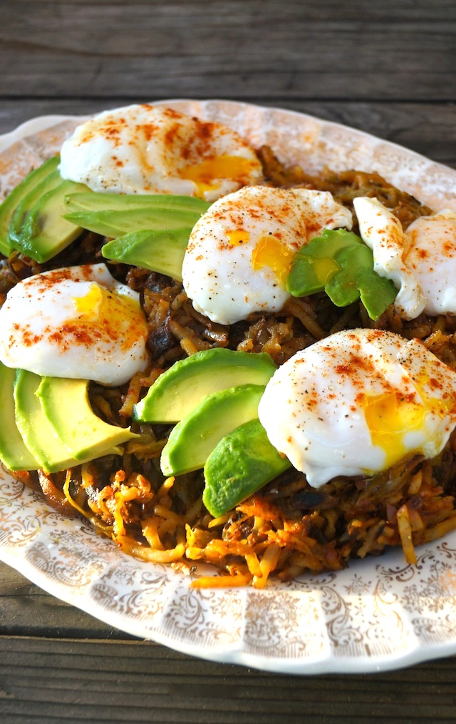 Perfect Poached Eggs Over Double Hatch Hash Browns on a gold rimmed, white serving dish with fresh avocado slices.