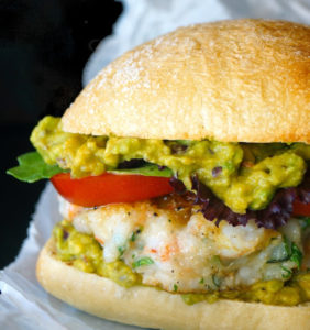 close up of shrimp burger with guacamole in a bun on parchment paper