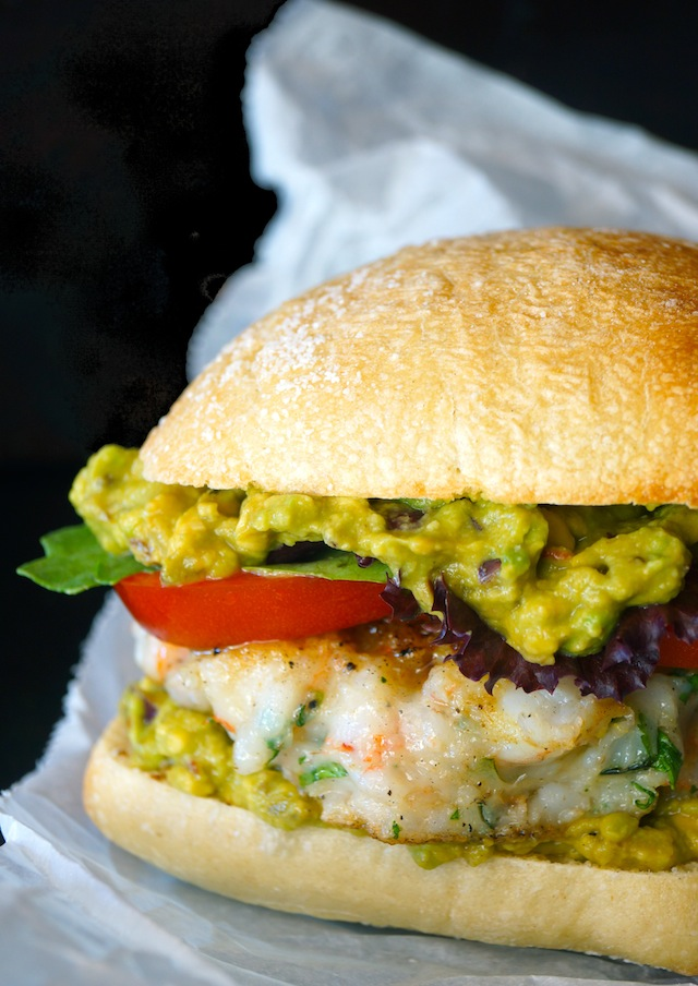 Shrimp burger with guacamole, tomato, lettuce and bun on parchment paper.