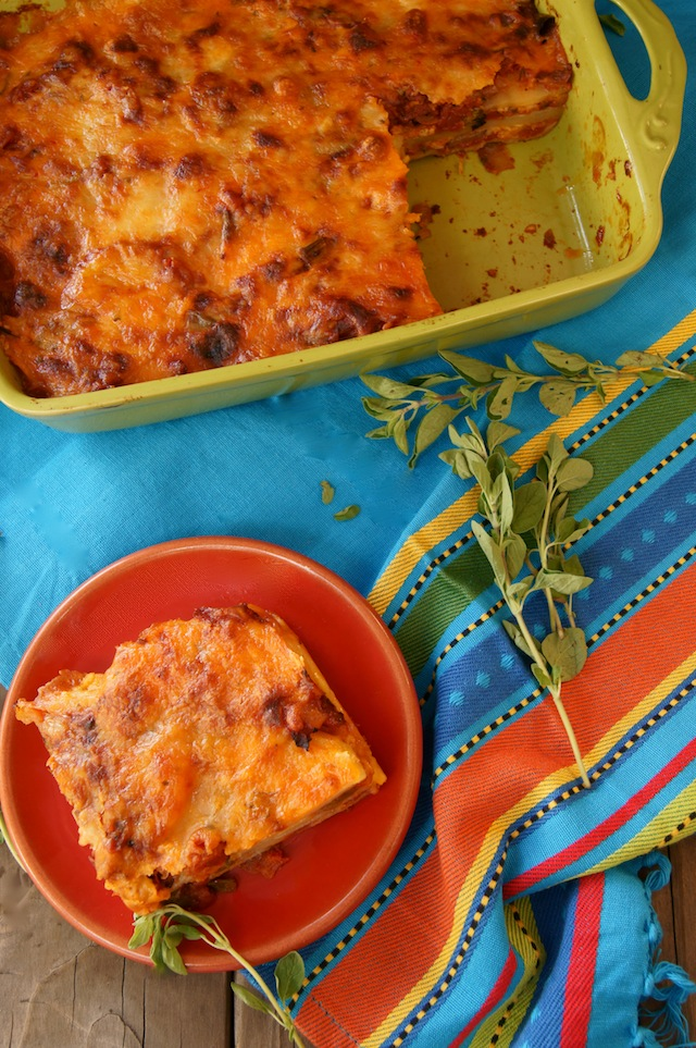 Chipotle-Potato Mexican Lasagna in a green baking dish, and one slice on a red plate.