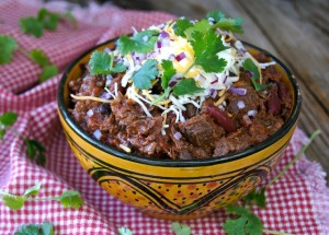 Chocolate Chipotle Colorado Style Chili in a ceramic golden bowl with cheese and cilantro on top.
