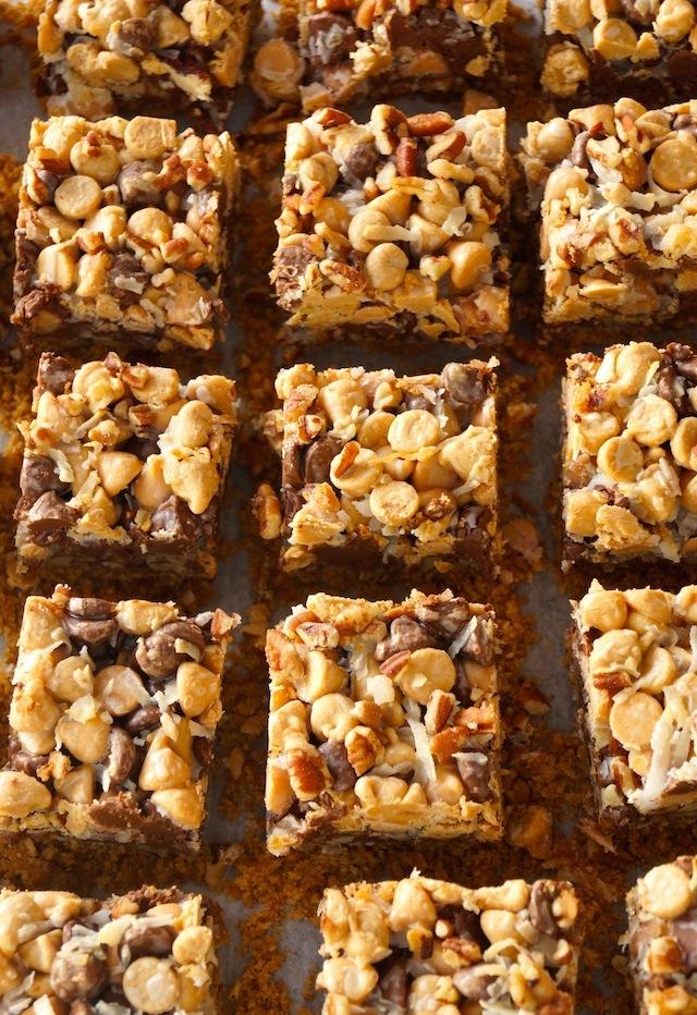Peanut Butter Pretzel Seven Layer Magic bars, cut into squares on parchment