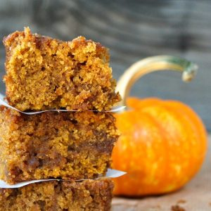 a few stacked slices of pumpkin coffee cake with small pumpkin