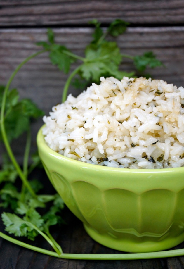 Coconut Cilantro Rice in a green bowl with cilantro sprigs in background