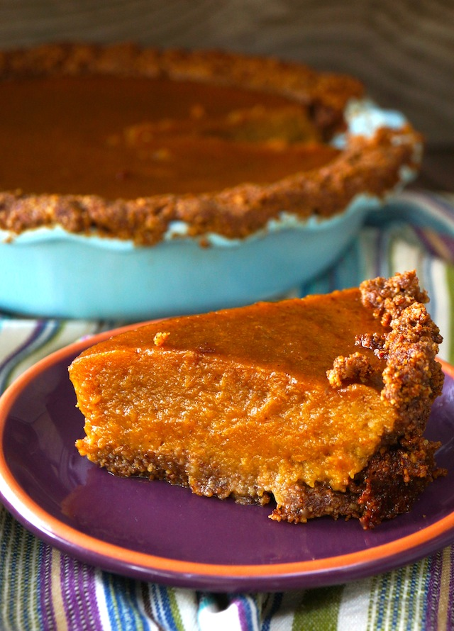 One slice of Gluten-Free Chai Spiced Butternut Squash Pie with Pecan-Walnut Crust on a purple plate with pie in light blue pie dish behind it.