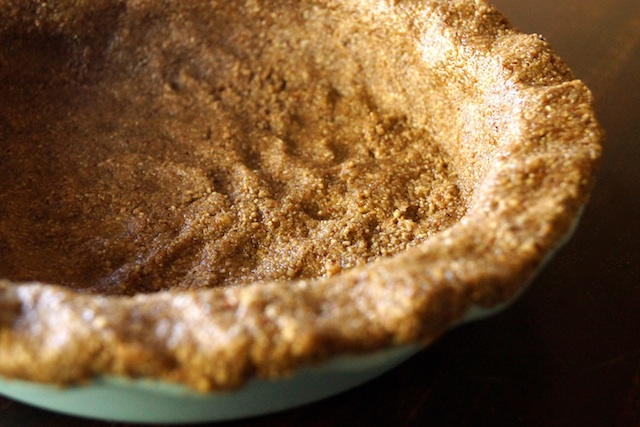 Nut crust pressed into a light blue pie plate.