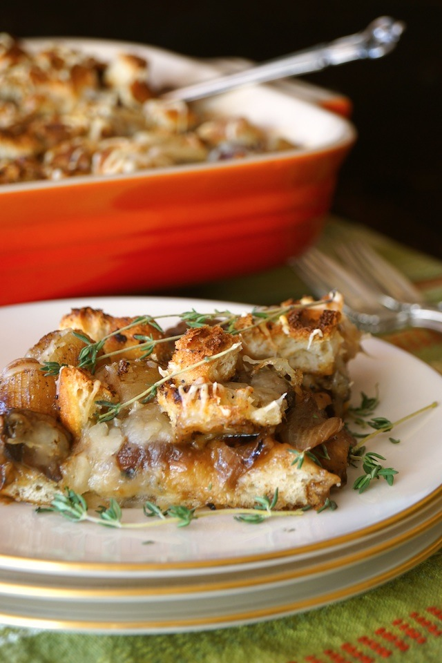 French Onion Mushroom Casserole Recipe sliced on a white plate with green thyme sprig and red dish in background