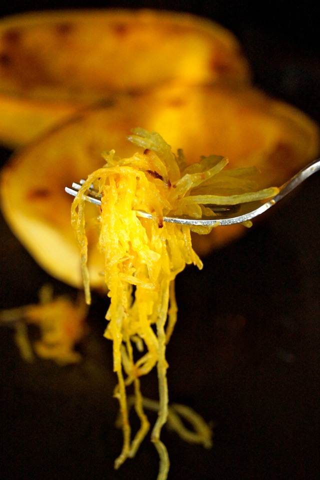 A fork full of cooked spaghetti squash in front of spaghetti squash halves.