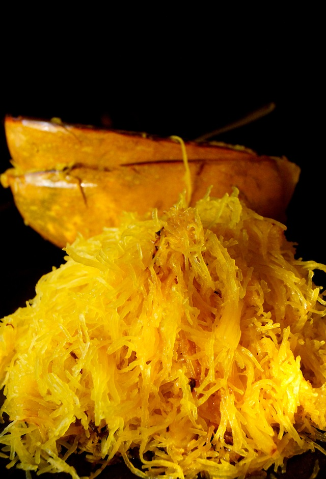 Big pile of spaghetti squash in front of two empt halves, black badkground.