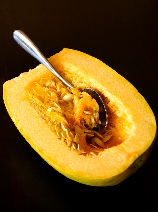 Half of a spaghetti squash with large metal spoon to remove seeds