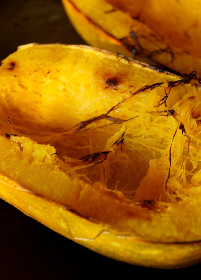 Half of a roasted spaghetti squash, round side down.