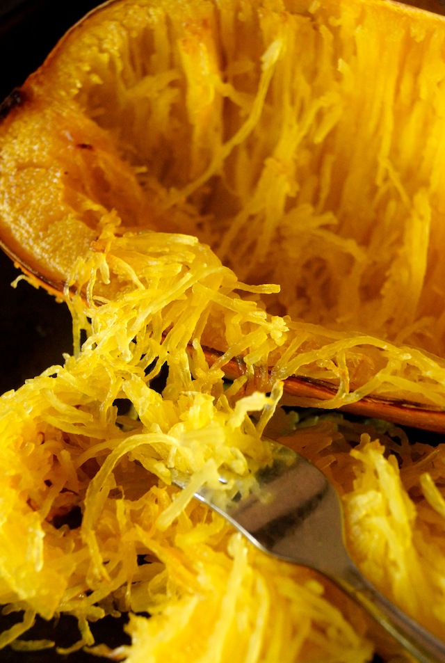 Cooked Spaghetti squash being removed from the inside of its skin with a fork.