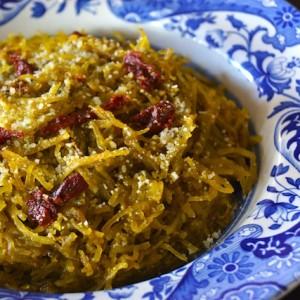 Tomato-Spinach Pesto Spaghetti Squash on a blue and white rimmed shallow bowl