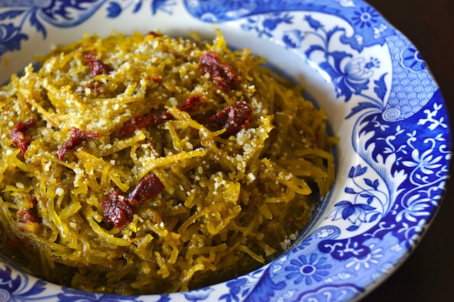 Tomato-Spinach Pesto Spaghetti Squash Recipe in a pretty blue and white-rimmed bowl, with sun-dried tomatoes on top.