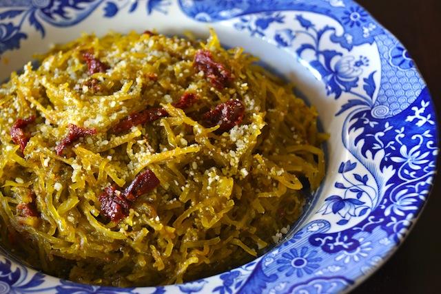 Pesto Spaghetti Squash Recipe in a pretty blue and white-rimmed bowl, with sun-dried tomatoes on top.