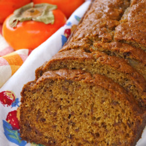 Sliced loaf of Ginger Persimmon Bread with fresh, whole persimmons