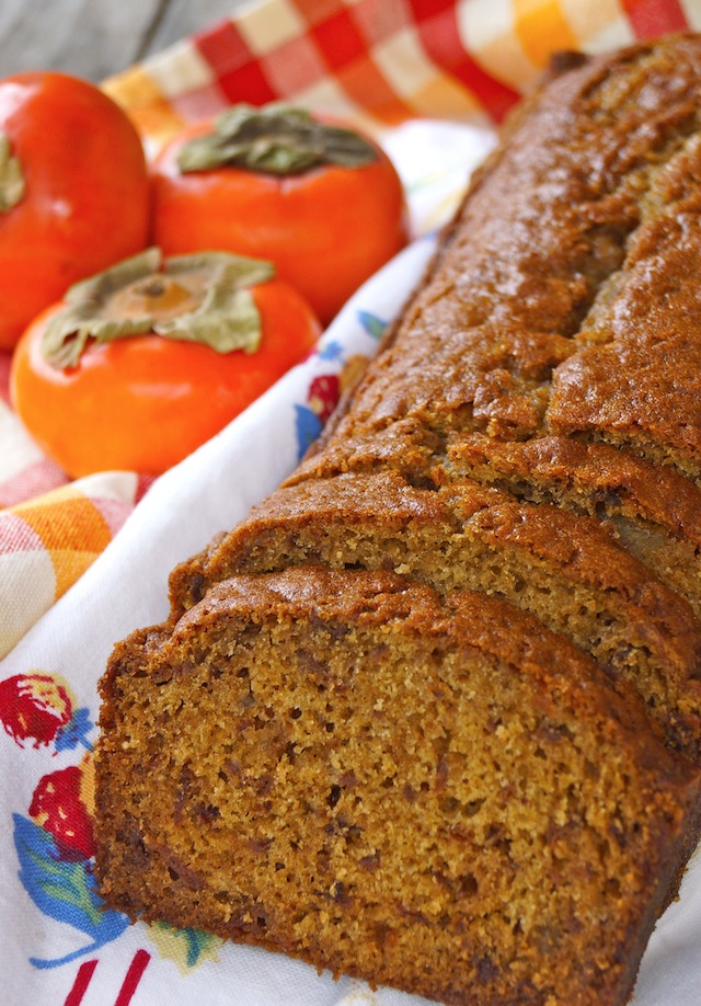 Persimmon Gingerbread loaf with a few slices and three whole bright orange persimmons