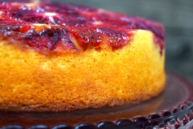 side view of Turmeric Blood Orange Upside Down Cake on a glass, pink cake stand