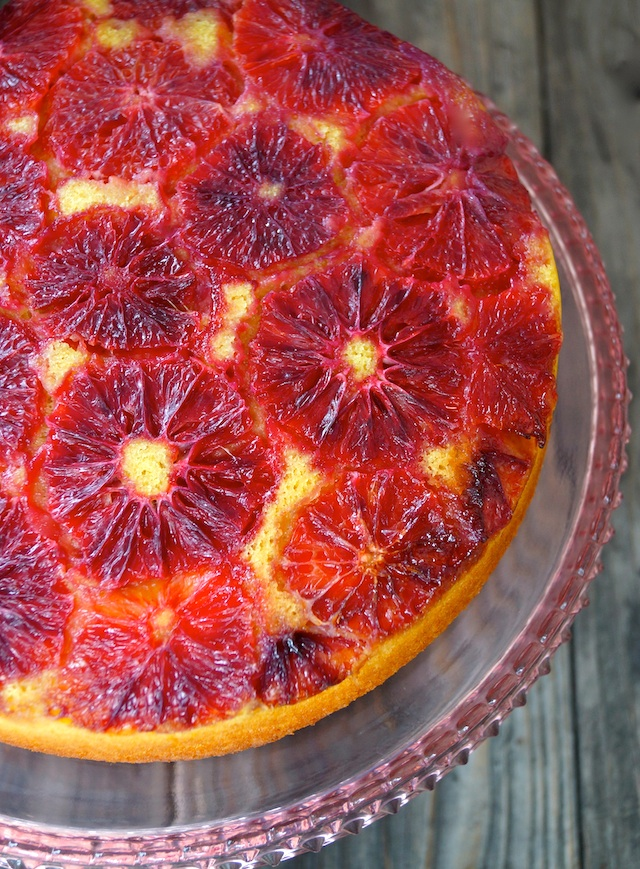 Turmeric Blood Orange Upside Down Cakeon a pink, glass cake stand