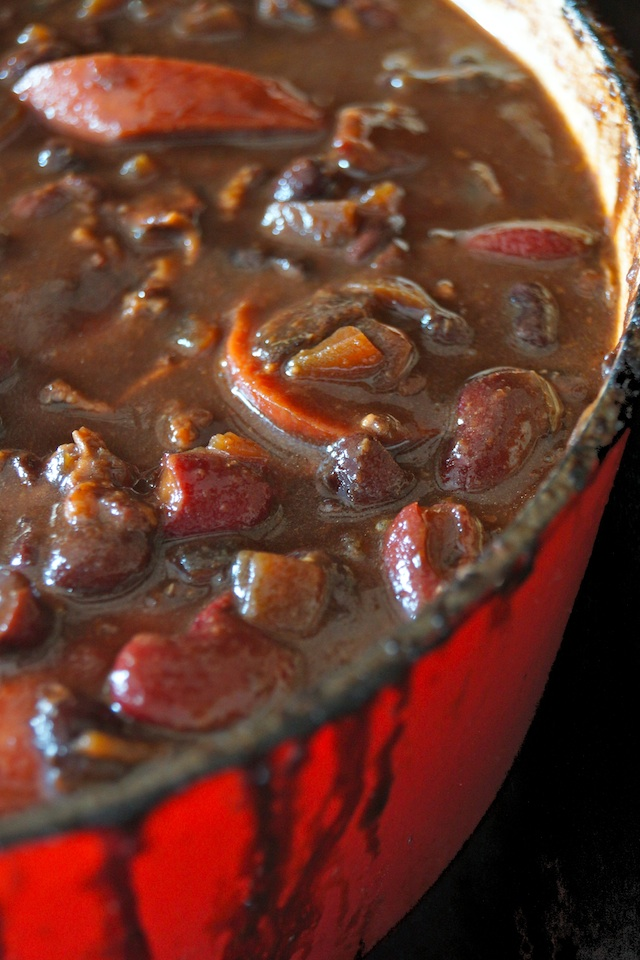 Knockwurst and the Best Baked Beans Ever in a red Dutch oven, spilling over the side a bit.