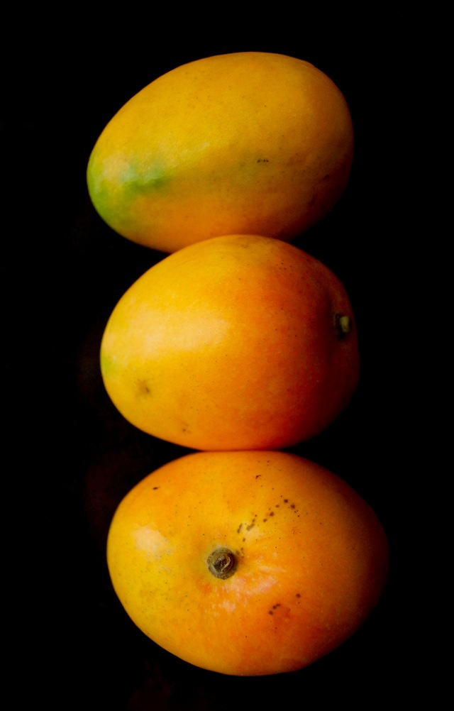 3 stacked Honey Gold Australian Mangoes with black background.