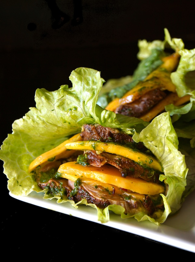 Mango Pork Lettuce Wrap with Chimichurri on white plate with black background.