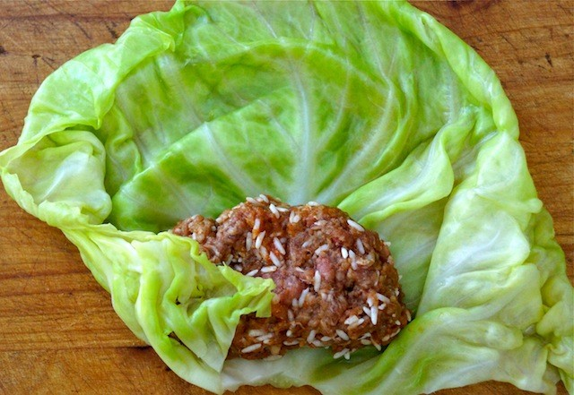 One beef and rice cabbage roll being wrapped on cutting board