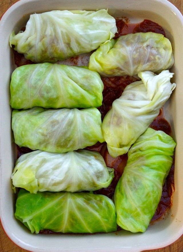 Stuffed Cabbage rolls on top of tomato sauce in baking pan