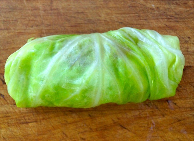 One wrapped cabbage roll on cutting board