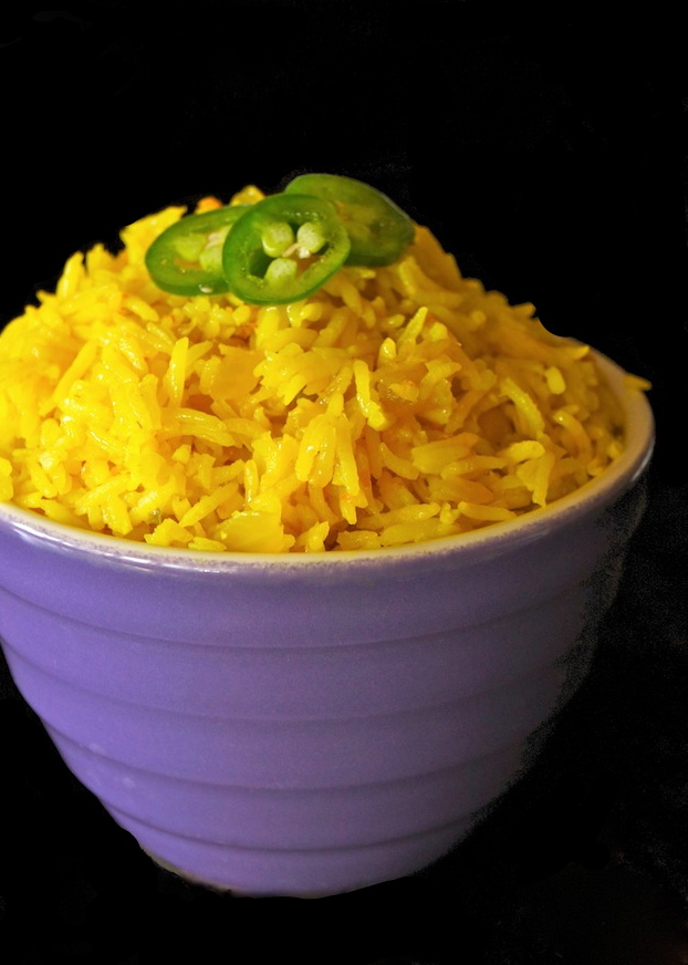Purple bowl with yellow rice with rice with sliced jalapenos on top.