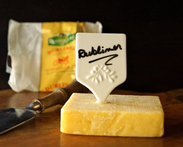 square chunk of Kerrygold Dubliner cheese with a white, ceramic cheese marker in the top