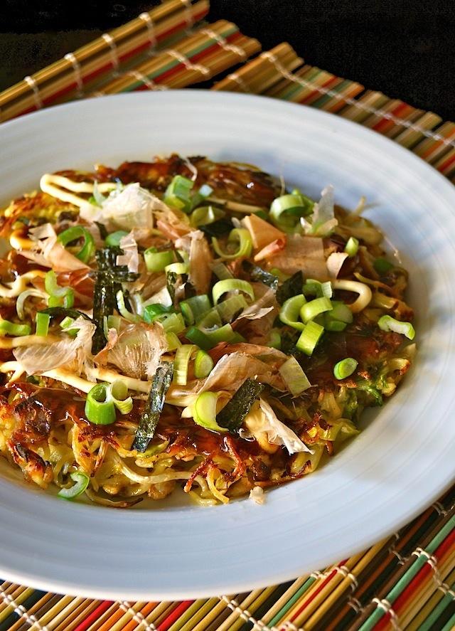 Yakisoba Okonomiyaki in white bowl on colorful bamboo mat