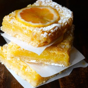 Three stacked Gluten-Free Lemon with Coconut Crust with parchment between them
